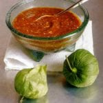 Smoky chipotle salsa with pan-roasted tomatillos in a glass bowl on a towel, two tomatillo in front