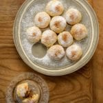 A plate of round Greek biscuit cookies with an apple filling, all dusted with powdered sugar