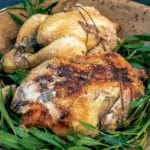 Two salt crust chickens on a bed of leaves and wooden plate