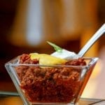 A glass dish of beef chili topped with cheddar cheese sauce and a dollop of sour cream with a spoon resting inside.