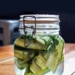 A small glass jar filled with sandwich pickles, rosemary, and thyme.