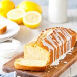 Ina Garten's lemon cake, a pound cake, on a cutting board, drizzled with a lemon glaze