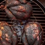 Three whole smoked chickens on a round grill.
