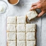 A frosted coconut sheet cake cut into 12 squares on a piece of parchment with a person grabbing a piece.