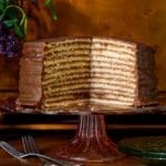 Trisha Yearwood's chocolate torte on a cake stand with a section cut from it to display 12 layers.