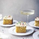 Squares of vanilla sheet cake with Swiss buttercream frosting and sprinkles on white plates with a coupe of Champagne in the background.