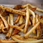 A tangle of baked fries on a rimmed baking sheet.