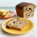 A cut loaf of cinnamon raisin swirl bread and a slice of it on a yellow plate with butter in the background
