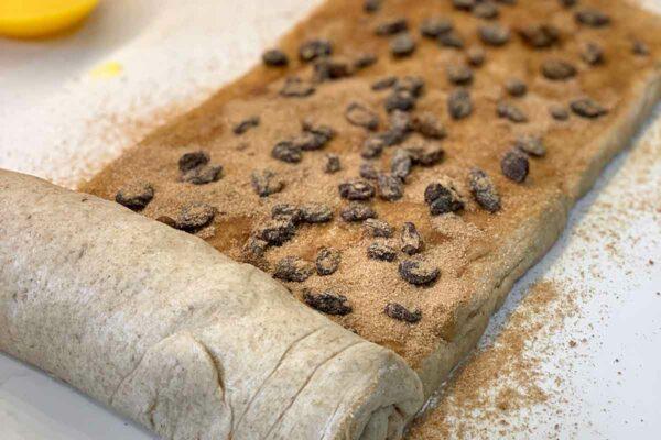 Cinnamon raisin swirl bread dough being rolled up.