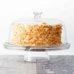 A whole coconut carrot cake, covered in toasted coconut on a glass cake stand, covered with a glass dome.