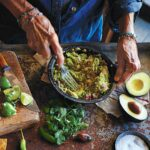 A person mashing avocado into a bowl of easy guacamole on a table with salt, avocado, cilantro, lime, and chiles.