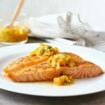 White plate with a fillet of Indian-spiced salmon with mango salsa on top