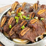 Strips of Korean beef barbecue on a platter, garnished with green onions and sesame seeds.
