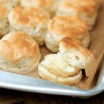 A rimmed baking sheet with rows of Southern buttermilk biscuits.