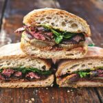 Steak sandwich pieces side-by-side and stacked on top of each other on a wooden table.