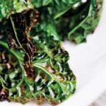 A few pieces of grilled kale stacked on a white plate.