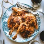 A spatchcocked mayo roast chicken on a blue and white plate with a salad and a bowl of salt and pepper nearby.