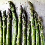 Ten spears of asparagus seasoned with salt and pepper and arranged in a row on a baking sheet.