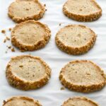 Ten Stilton and walnut crackers arranged in rows on a sheet of parchment.