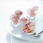 Three glass bowls filled with scoops of strawberry cheesecake ice cream.