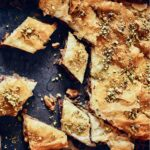 Diamond-shaped pieces of walnut baklava, topped with chopped pistachios.