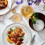 A patterned plate topped with chicken thighs with spicy peach sauce on a table with a bottle and glass of wine, flowers, cutlery, and a napkin.