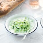 A bowl of chilled cucumber soup with a spoon resting inside.