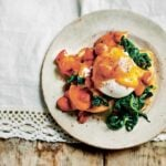 A plate topped with a serving of chorizo eggs benedict - chorizo hollandaise, garlicky spinach, and poached egg on toast.