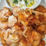 A white oval platter holding a bowl of dill dip with potato chips beside it.
