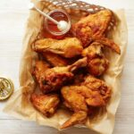 A basket of fried chicken with a jar of honey on the side.