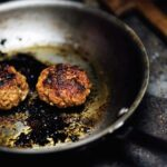 Two patties of Goan-style chourico being cooking in a metal skillet.