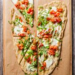 A grilled pizza with summer tomato sauce and scallions, cut into 8 wedges on a wooden board.