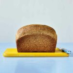 A loaf of unsliced whole wheat bread sitting on a yellow cutting board with a blue-handled knife beside it