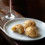 A white plate with three prosciutto-cheese gougeres with a glass of Prosecco in the background.