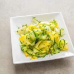 A tangle of sautéed summer squash ribbons on a square white plate.