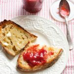 Two pieces of buttered toast, one with strawberry jam, on a white plate with a spoon and jar of jam in the background.