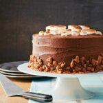 A s'mores cake, topped with toasted marshmallows and graham cracker crumbles on a cake stand.