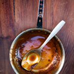 A small pot with a small amount of spicy bourbon barbecue sauce left in it and a spoon resting inside.