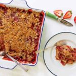 A square baking dish filled with strawberry rhubarb crumble with balsamic drizzle, with a portion on a plate and a few strawberries on the side.