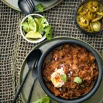 A bowl of Texas-style chili with pork and brisket with a fork, spoon, and bowls of lime, cilantro, and pickled jalapenos on the side.