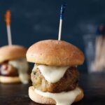 A chicken meatball on a slider bun with a toothpick skewered through it.