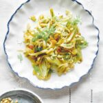 A white and blue bowl filled with fennel, dill, pine nuts, and golden raisins on a white tablecloth.