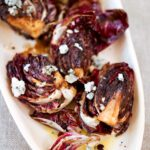 A white platter, piled with quartered grilled radicchio topped with crumbled Gorgonzola cheese.