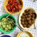 A platter of lamb meatballs with yogurt sauce, tomatoes, and cucumbers in bowls on the side.