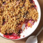 A white bowl filled with blueberry nectarine crisp with a scoop missing and a spoon laying beside it.