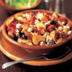 A terracotta dish filled with potatoes, feta, black olives, and tomatoes.