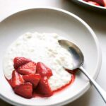 A bowl of rice pudding with a spoon and a scoop of halved strawberries and juice