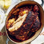 A cast-iron Dutch oven filled with a deeply roasted chicken, flanked by a bag of potato chips.