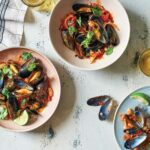 Three bowls of smoky chile and tomato mussels, on a table flanked by a glass of beer and a few empty mussel shells.
