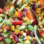 A close up of two serving spoons in a bowl of corn, lima beans, chopped peppers, red onion and cherry tomatoes, dressed with parsley, mint, and dressing.